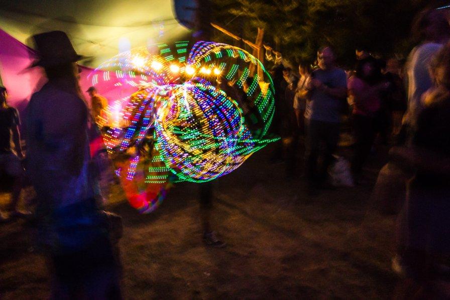 A festival-goer twirls a lighted hula hoop
